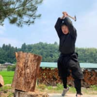 Genichi Mitsuhashi chops wood in Iga, Mie Prefecture, on June 21. Mitsuhashi has become the first student ever to graduate from a Japanese university with a master's degree in ninja studies.  | GENICHI MITSUHASHI / AFP-JIJI