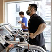A man uses a running machine at a gym in the city of Osaka on June 1. Some of the machines were idled to maintain social distancing as concerns over the coronavirus linger.  | KYODO