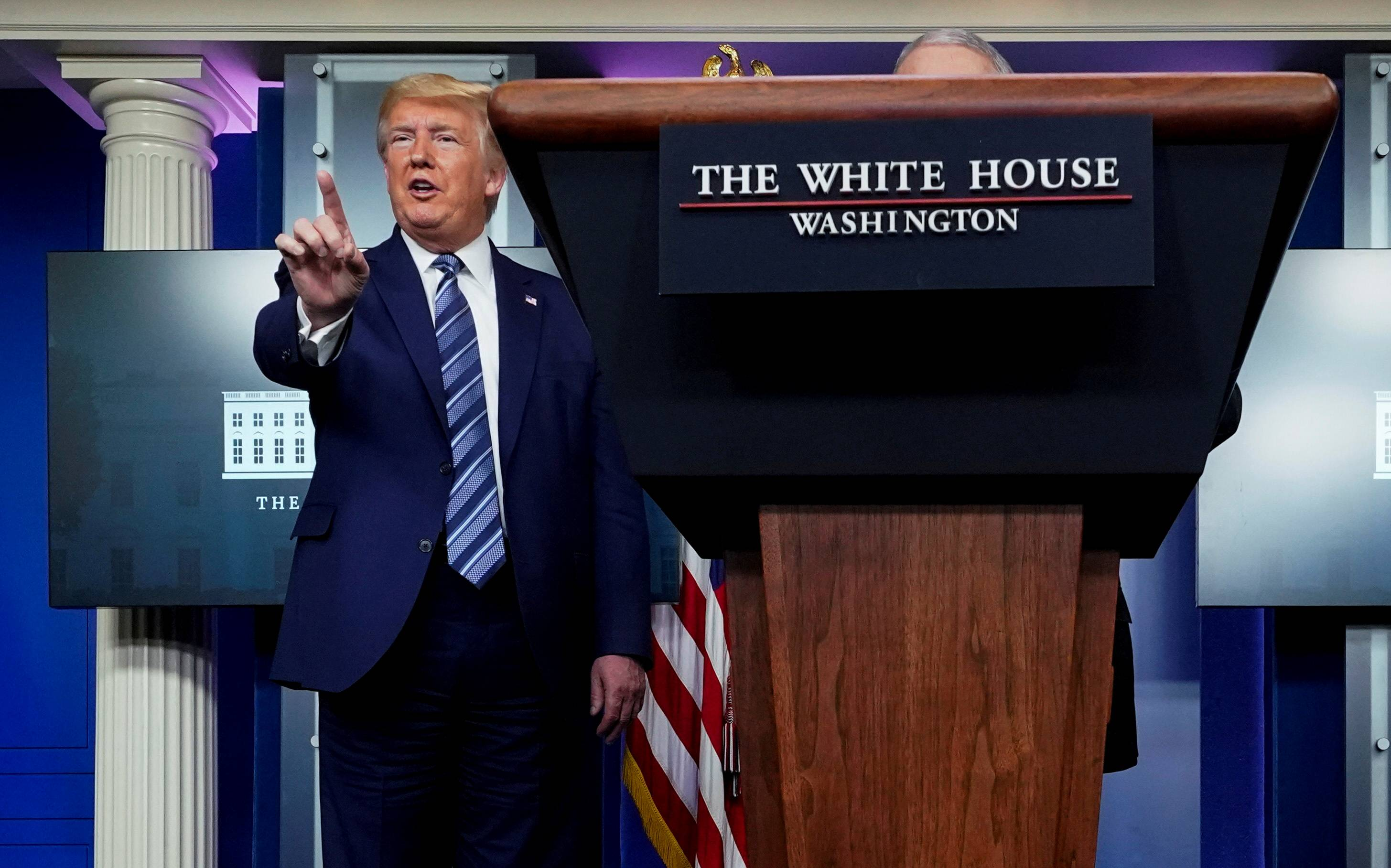U.S. President Donald Trump stops a reporter from asking Dr. Anthony Fauci a question about use of the drug hydroxychloroquine to treat COVID-19, at the White House on April 5. | REUTERS