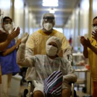A patient gestures as he leaves the Nossa Senhora da Conceicao Hospital after being treated for COVID-19 in Porto Alegre, Brazil, in April.  | REUTERS