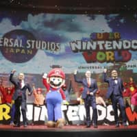 Mario and officials pose for a photo in Osaka in January at a news conference to announce a plan to open the Nintendo-themed area in Universal Studios Japan. | KYODO