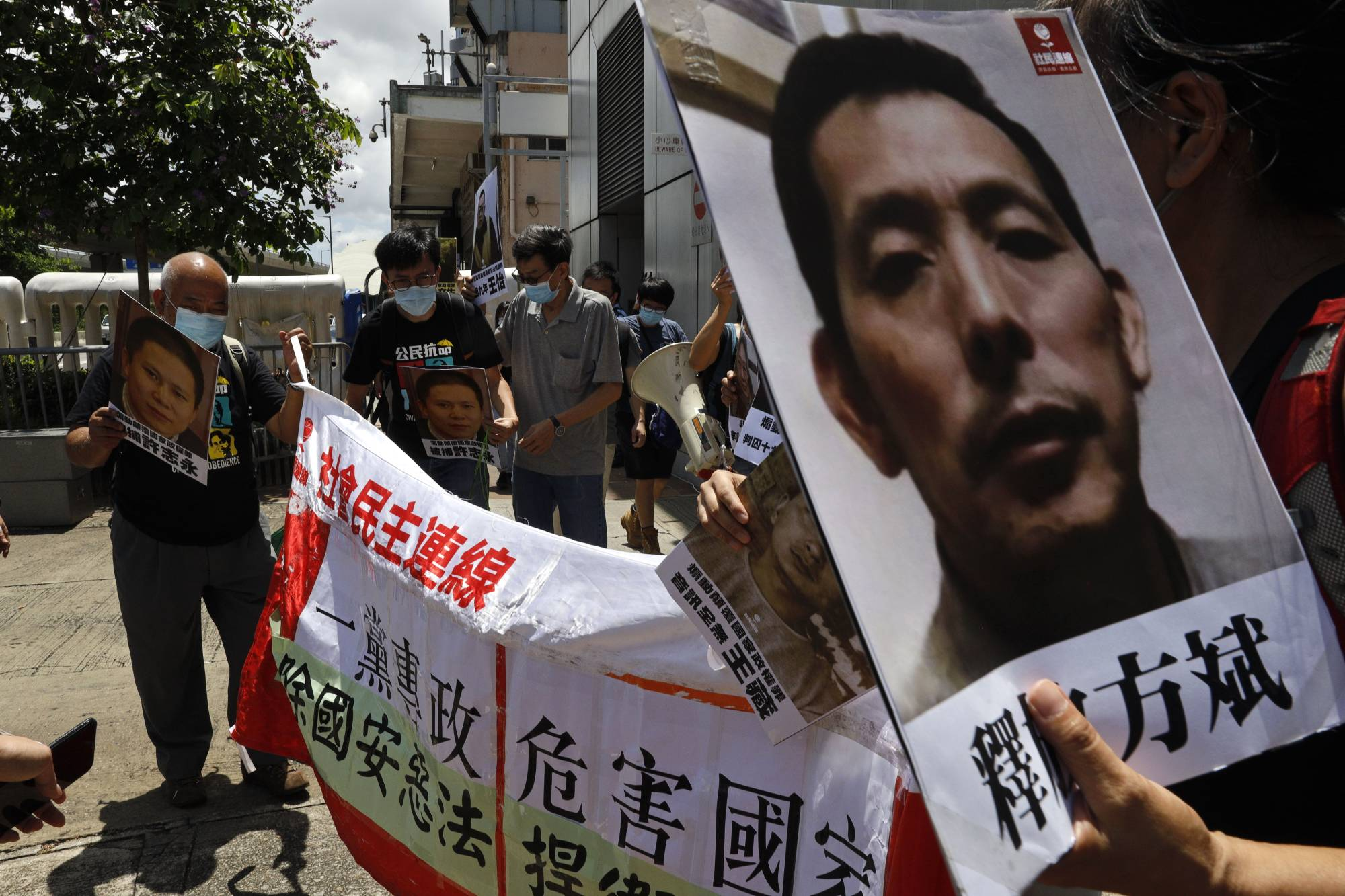 Pro-democracy demonstrators hold up portraits of jailed Chinese civil rights activists, lawyers and legal activists as they march to the Chinese liaison office in Hong Kong on Thursday.  | AP