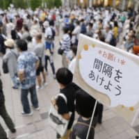 People listen to a candidate's speech at a Tokyo gubernatorial election event in the capital on Saturday alongside a signboard asking them to maintain a proper distance from each other.   KYODO