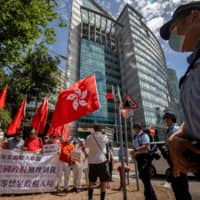 Protestors wave flags outside the Commissioner's Office of China's Foreign Ministry in Hong Kong, China, on Monday. | BLOOMBERG
