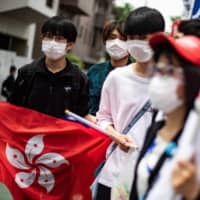 A group of pro-democracy activists hold a Hong Kong flag as they walk to the Chinese Embassy in Tokyo during a protest march on June 4. | AFP-JIJI