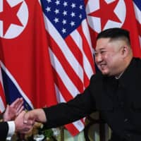 U.S. President Donald Trump shakes hands with North Korean leader Kim Jong Un following a meeting in Hanoi in February 2019. | AFP-JIJI