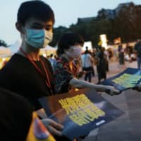 Volunteers hand out posters supporting Hong Kong's anti-government movement in Taipei on June 13. | REUTERS