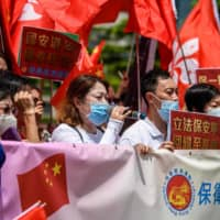 Pro-China supporters display Chinese and Hong Kong flags during a rally near the government headquarters in Hong Kong on Tuesday, as China passed a sweeping national security law for the city. | AFP-JIJI