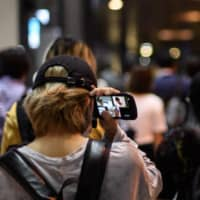 People hold their smartphones as they have a conversation via the Zoom mobile app in Tokyo's Shinjuku Ward on June 24.  | AFP-JIJI