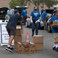 Staff and volunteers with The Los Angeles Dodgers Foundation distribute food and other goods for people facing economic hardship in Huntington Park, California, on June 18. | AFP-JIJI