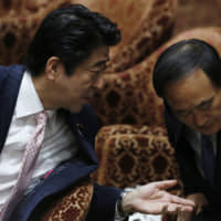 Prime Minister Shinzo Abe speaks to Chief Cabinet Secretary Yoshihide Suga before Suga answers questions during a Lower House Budget Committee session at the Diet in Tokyo in February 2014.  | REUTERS