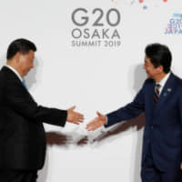 Chinese President Xi Jinping is welcomed by Prime Minister Shinzo Abe upon his arrival for a family photo session at at the Group of 20 summit in Osaka last June. China hawks among Japan's conservatives, long divided on Beijing, have gained ground recently as its diplomatic and military clout grows. | POOL / VIA REUTERS