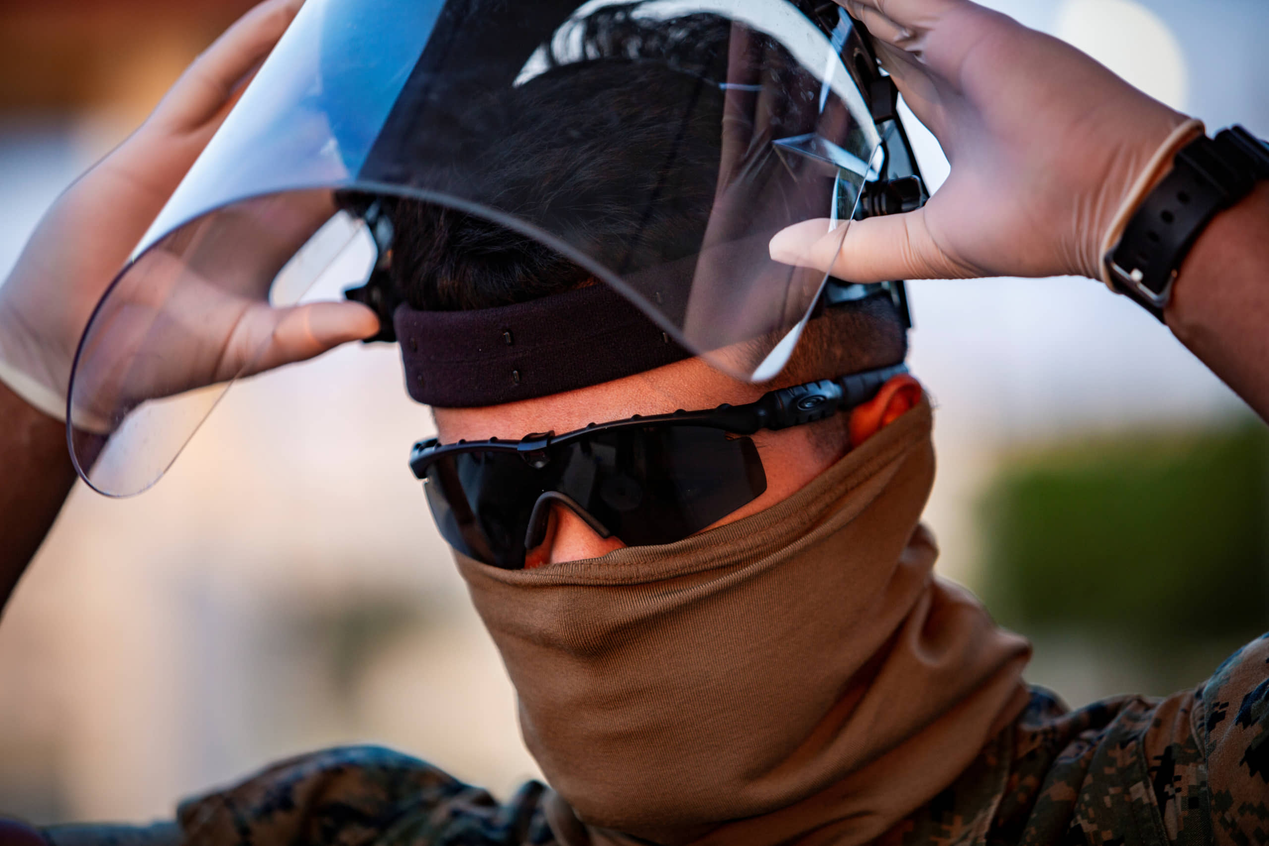 A U.S. Marine dons personal protective equipment (PPE) to begin screening incoming personnel in response to the increased threat of COVID-19 at Camp Foster, in Okinawa Prefecture, in April 10. | U.S. MARINE CORPS / VIA REUTERS