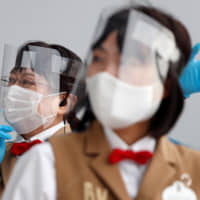 Tokyo Disneyland staff members wearing protective masks and face shields greet visitors during the reopening of Tokyo Disneyland and Tokyo DisneySea after months of closure due to the coronavirus pandemic, in Urayasu, Chiba Prefecture, on Wednesday. | REUTERS