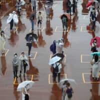 Visitors practice social distancing while waiting to enter Tokyo Disneyland and DisneySea in Urayasu, Chiba Prefecture, on Wednesday during the theme parks' rainy reopening. | REUTERS