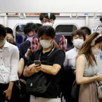 Passengers wearing masks ride a subway train in Tokyo on July 3. | REUTERS