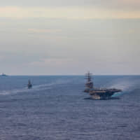 Maritime Self-Defense Force training vessels Kashima and Shimayuki conduct an exercise with the USS Ronald Reagan aircraft carrier in the South China Sea on July 7. | U.S. NAVY / VIA REUTERS