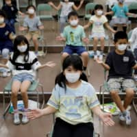 Students wearing protective face masks clap along instead of singing a song during a music class at Takanedai Daisan elementary school, which practices various methods of social distancing in order to prevent the infection, in Funabashi, east of Tokyo, on July 16. | REUTERS