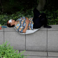 A man uses his mask to cover his eyes while taking a nap in Tokyo on Thursday. | REUTERS