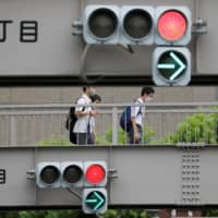 Men wearing protective face masks are seen through traffic signals amid the coronavirus disease outbreak in Tokyo on July 29. | REUTERS