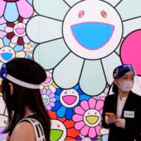Staff members wear face shields next to 'Pop up flower' by artist Takashi Murakami during a media preview of 'STARS: Six Contemporary Artists from Japan to the World' at the Mori Art Museum in Tokyo on July 30. | AFP-JIJI