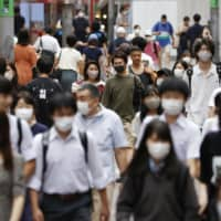 People wearing masks to prevent the spread of the new coronavirus walk in Tokyo's Shibuya Ward on Saturday. | KYODO