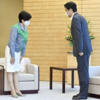 Tokyo Gov. Yuriko Koike and Prime Minister Shinzo Abe greet each other as they meet at the Prime Minister's Office in Tokyo on Monday.   KYODO