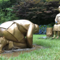 A statue of a girl symbolizing so-called comfort women is seen on the grounds of the Korea Botanic Garden in Pyeongchang along with a statue of a man bowing. | YONHAP / VIA KYODO