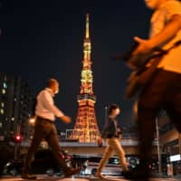 People wearing face masks walk on a street near Tokyo Tower in the capital on Monday evening. | AFP-JIJI