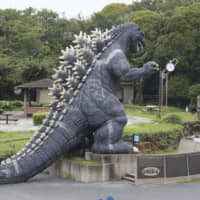 A woman wearing a face mask to protect against the spread of the new coronavirus stands near a Godzilla's slide at Kurihama flower park in Yokosuka, near Tokyo Wednesday, July 15, 2020. (AP Photo/Koji Sasahara)