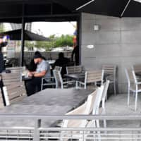 A waiter walks past a few customers dining outdoors at a restaurant in Los Angeles on Monday, a day after the state's governor ordered the immediate closure of bars in a number of California counties.  | AFP-JIJI