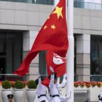 The flags of China and Hong Kong are raised during a ceremony to mark the 23rd anniversary of Hong Kong's return to Chinese rule on Wednesday in the financial hub. | BLOOMBERG