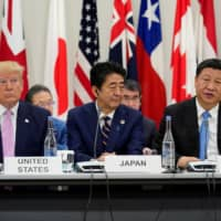 Prime Minister Shinzo Abe is flanked by U.S. President Donald Trump and Chinese leader Xi Jinping during a meeting at the Group of 20 leaders summit in Osaka in June last year. Tokyo, wary of repercussions from Beijing, finds itself in a dilemma as it faces calls from Washington and others to help safeguard rights of the city's residents.   REUTERS