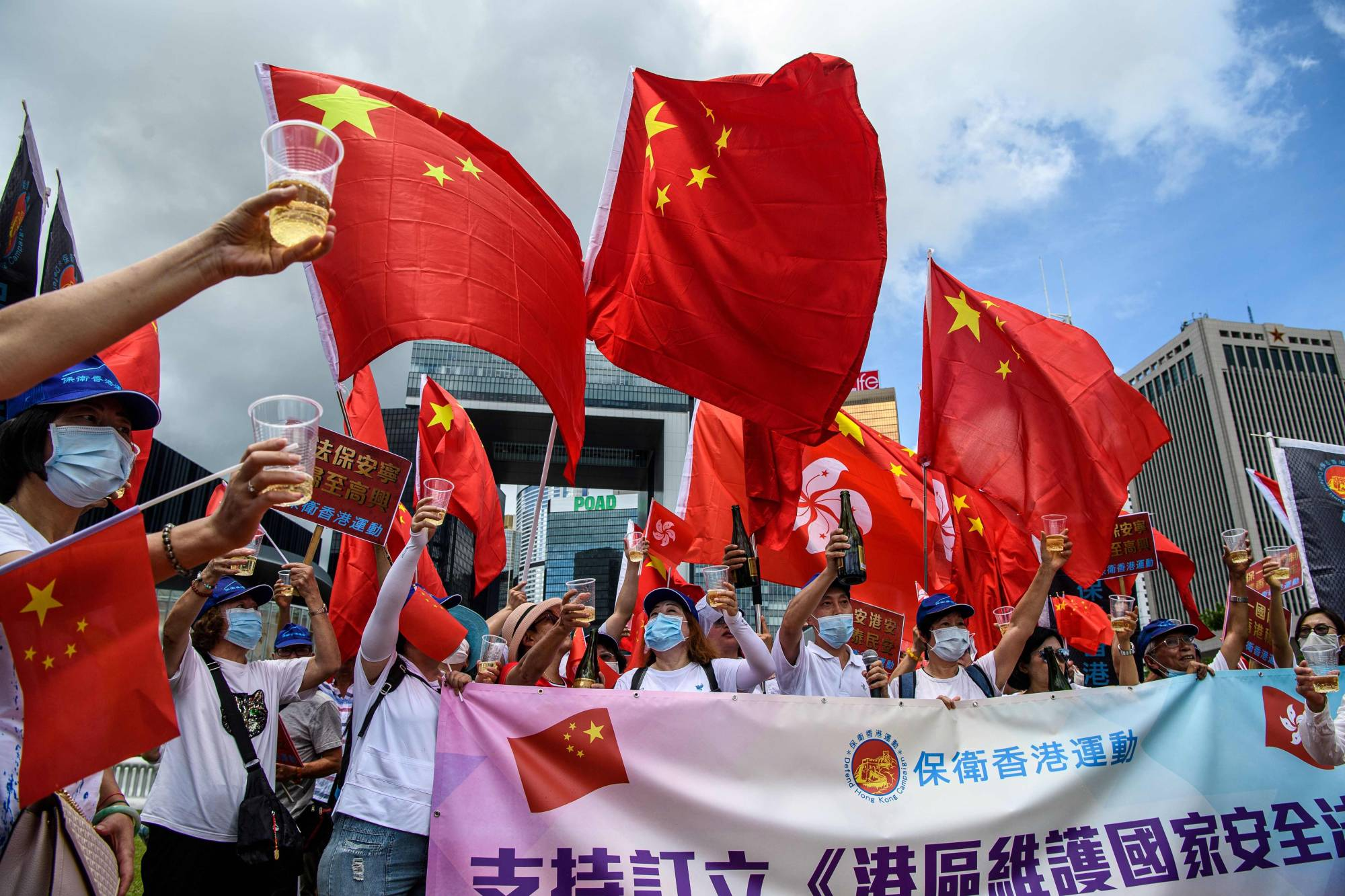 Pro-China supporters display Chinese and Hong Kong flags as they raise a toast with champagne during a rally near the government headquarters in Hong Kong on Tuesday after Beijing passed a sweeping national security law for the city.   AFP-JIJI