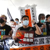 Pro-democracy protesters shout slogans as they march toward a flag-raising ceremony in Hong Kong on Wednesday. The city marked the 23rd anniversary of its handover to China in 1997, one day after China enacted a national security law that cracks down on protests in the territory.   AP