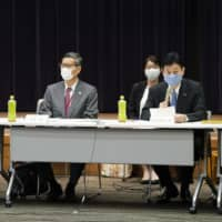 Health minister Katsunobu Kato (left), Shigeru Omi of the Japan Community Healthcare Organization (center), and Yasutoshi Nishimura, minister in charge of virus response, attend an advisory panel meeting of health experts in Tokyo on May 25.   KYODO