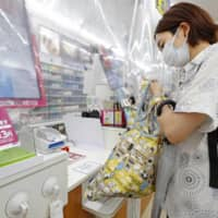 A woman puts items she has purchased into her shopping bag at a convenience store in Shinagawa Ward, Tokyo, on Wednesday. Stores nationwide are now charging for plastic bags. | KYODO