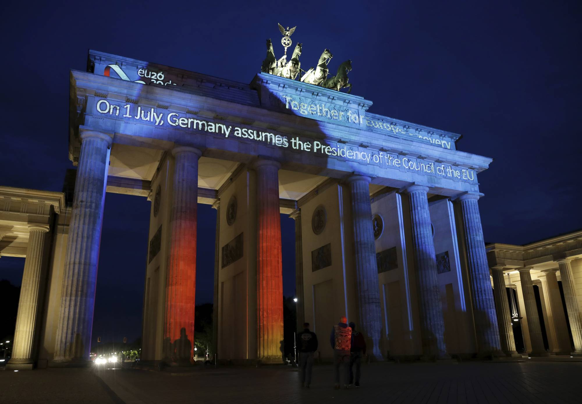 The Brandenburg Gate is illuminated on Monday to mark Germany's July 1 assumption of the EU Council presidency. The European Union's largest economy is taking the chair of the 27-nation bloc amid massive challenges and huge expectations as the continent grapples with the fallout from the coronavirus pandemic. | AP