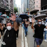 Anti-national security law protesters march on Wednesday in Hong Kong.  | REUTERS