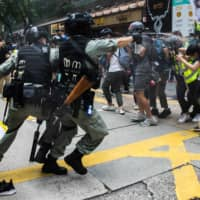 Riot police deploy pepper spray toward journalists and protesters in Hong Kong on Wednesday.  | AFP-JIJI