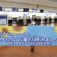 Staff of All Nippon Airways put up a banner to celebrate the restart of their counter service at Haneda Airport in Tokyo on Wednesday. | KYODO