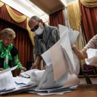 Members of a local electoral commission count ballots at a polling station after a nationwide vote on constitutional reforms, in Moscow on Wednesday.  | AFP-JIJI