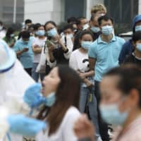 People line up for coronavirus testing at a factory in Wuhan, China, in May. | CHINATOPIX / VIA AP