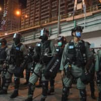 Riot police stand guard after pushing back protesters demonstrating against Hong Kong's new security law on Wednesday.  | AP