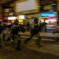 Police charge towards protesters during a rally against a new national security law in Hong Kong on Wednesday.  | AFP-JIJI