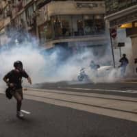 Riot police deploy tear gas as they clear protesters from a road during a rally against a new national security law in Hong Kong on Wednesday.  | AFP-JIJI