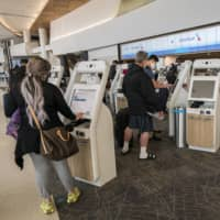 Travelers use kiosks to check in at the American Airlines counter at San Francisco International Airport on Wednesday as the carrier opted to return to operation with fully loaded flights despite the pandemic. | BLOOMBERG