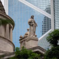 A Statue of Justice stands above the Court of Final Appeal building in the Central district in Hong Kong in June. Just hours after the financial hub's controversial new security law came into effect Tuesday, Taiwan officially opened an office dedicated to making migration easier for Hong Kong residents and companies.   BLOOMBERG