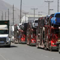 Carrier trailers transport Toyota vehicles for delivery while queuing at the border for customs control to cross into the U.S. on Tuesday. | REUTERS