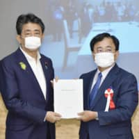 Yoshimitsu Kobayashi (right), head of the Regulatory Reform Promotion Council, hands a set of proposals to Prime Minister Shinzo Abe at the Prime Minister's Office on Thursday. | KYODO